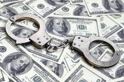 Ложь наручников полиции на много долларовых банкнотах Концепция противозаконного владения денег, противозаконных сделок с доллара стоковые фото