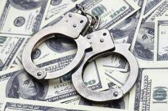 Ложь наручников полиции на много долларовых банкнотах Концепция противозаконного владения денег, противозаконных сделок с доллара стоковое фото rf