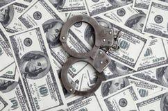 Ложь наручников полиции на много долларовых банкнотах Концепция противозаконного владения денег, противозаконных сделок с доллара стоковые фотографии rf