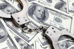 Ложь наручников полиции на много долларовых банкнотах Концепция противозаконного владения денег, противозаконных сделок с доллара стоковое изображение