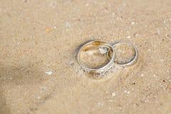 Ложь обручальных колец на песке Стоковые Изображения
