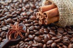 Ложь ручек циннамона на кофейных зернах Ложка сделанная из темного шоколада с цветком ани лежит на кофейных зернах стоковые фото