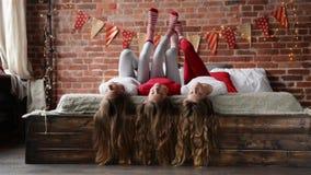 Ложь 3 сестер на кровати Тройни играя с ее длинными волосами в спальне украшенной для рождества весело видеоматериал