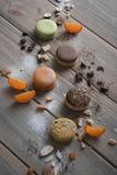 Ложь Macarons пестротканая на деревянном столе с различными ингредиентами, шоколадом, кофе, tangerines и больше стоковое фото rf