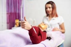 Лож девушки на кресле косметологии показывают ее класс жеста пальца Стоковая Фотография RF