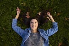 Лож девушки outstretched рукоятки на изумрудной траве Стоковые Изображения