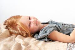 Лож и улыбки девушки сладостно стоковое изображение