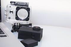 Лож камеры действия рядом с компьтер-книжкой Около коробки для подводной стрельбы и запасной батареи Стоковая Фотография RF