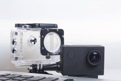 Лож камеры действия рядом с компьтер-книжкой Около коробки для подводной стрельбы и запасной батареи Стоковые Фотографии RF