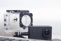 Лож камеры действия рядом с компьтер-книжкой Около коробки для подводной стрельбы и запасной батареи Стоковое фото RF