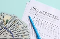 1065 лож налоговой формы около 100 долларовых банкнот и голубой ручки на светлом - голубая предпосылка Возвращение США для дохода стоковое изображение