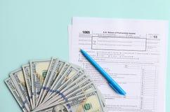 1065 лож налоговой формы около 100 долларовых банкнот и голубой ручки на светлом - голубая предпосылка Возвращение США для дохода стоковые изображения rf