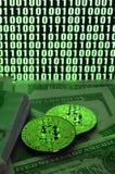 2 лож bitcoins на куче долларовых банкнот на предпосылке монитора показывая бинарный код ярких ых-зелен нулей и одного u Стоковая Фотография RF