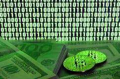 2 лож bitcoins на куче долларовых банкнот на предпосылке монитора показывая бинарный код ярких ых-зелен нулей и одного u Стоковые Изображения