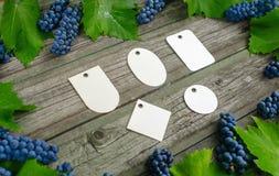 Лоза с голубыми виноградинами и листьями вокруг на винтажном деревенском деревянном столе Комплект шаблона бирок differents бумаж Стоковое фото RF