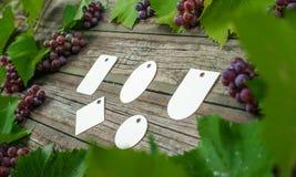 Лоза с розовыми виноградинами и листьями вокруг на винтажном деревенском деревянном столе Комплект бирок differents бумажных Стоковая Фотография RF