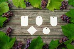 Лоза с розовыми виноградинами и листьями вокруг на винтажном деревенском деревянном столе Комплект шаблона бирок differents бумаж Стоковое фото RF