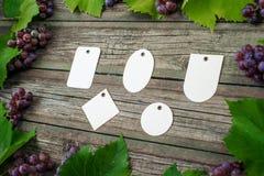 Лоза с розовыми виноградинами и листьями вокруг на винтажном деревенском деревянном столе Комплект шаблона бирок differents бумаж Стоковые Фотографии RF