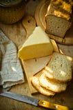 Ломоть сыра, хлебца хлеба sourdough на деревянной разделочной доске, linen салфетке, деревенском интерьере кухни Стоковое Изображение RF