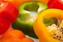 Ломтики красного, зеленого, желтого и померанцового перца изолированного на белой предпосылке Стоковые Изображения