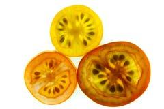 Ломтики красных, желтых, и померанцовых томатов виноградины на белой предпосылке Стоковое Изображение
