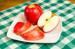 Ломтики яблока розовой повелительницы на белой плите Стоковые Фотографии RF