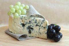 Ломтик голубого сыра с виноградинами на деревянной предпосылке Стоковые Фотографии RF