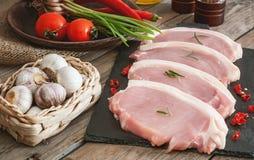 Ломти свинины на шифере всходят на борт с розмариновым маслом стоковые изображения rf