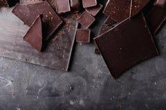 Ломти шоколада Части шоколадного батончика Большой бар шоколада на серой абстрактной предпосылке Конфеты шоколада Стоковое Изображение RF