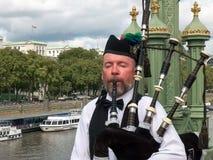 ЛОНДОН, АНГЛИЯ, ВЕЛИКОБРИТАНИЯ - 17-ОЕ СЕНТЯБРЯ 2015: плательщик волынок выполняет на мосте над рекой thames в Лондоне стоковые изображения