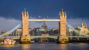 Лондон, Англия - мост башни мира известный на золотом восходе солнца с красным двухэтажным автобусом Собор ` s StPaul Стоковые Фото