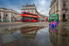 Лондон, Англия - 03 15 2018: Отражение красных двухэтажных автобусов на движении на цирке Piccadilly с великобританским зонтиком Стоковая Фотография RF