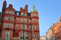 ЛОНДОН, ВЕЛИКОБРИТАНИЯ: Викторианец красного кирпича расквартировывает фасады в квадрате Беркли и улицу держателя в городе Вестми стоковые фото