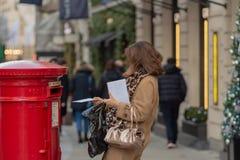 Лондон, Великобритания - 17, декабрь 2018: Письмо падения женщины в положении postbox красного цвета традиционном викторианском в стоковое фото
