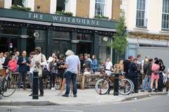 Лондон, Великобритания - 27-ое августа 2018: Пестрая толпа Лондона выпивая пиво вне паба стоковая фотография rf