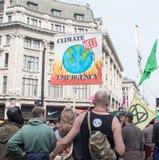 Лондон, Великобритания, 17-ое апреля 2019 - протестующие держат знамя и флаг на протесте изменения климата вне подполья цирка Окс стоковые фото