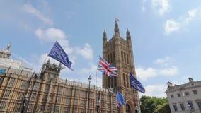 Лондон/Великобритания - 26-ое июня 2019 - флаги Европейского союза и Юниона Джек задержанные вне парламента Великобритании протес сток-видео