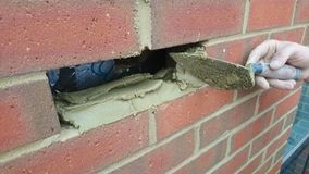 Лондон Великобритания 18/10/2017 Починка каменщика новый кирпич в стене нового дома Стоковые Фотографии RF