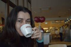 Лондон Великобритания 09/10/2017 Счастливый кофе питья клиента в Косте Стоковое Изображение
