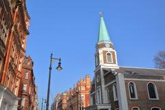 ЛОНДОН, ВЕЛИКОБРИТАНИЯ: Часовня Grosvenor и викторианец красного кирпича расквартировывают фасады в городе улицы s Audley Вестмин стоковые изображения
