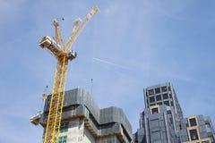 ЛОНДОН - МАЙ 2017: Кран и современные здания под конструкцией против голубого неба, в городе Лондона стоковые изображения
