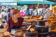 ЛОНДОН - 12-ОЕ ИЮНЯ 2015: Неопознанные посетители на сыре глохнут на рынке города Рынок города самое большое marke изысканной еды Стоковые Изображения