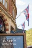 Лондон, Англия - 30-ое августа 2016: Объявление Co больших великобританских рыб внешнее с флагом Англии на заднем плане Стоковое Изображение RF