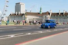 Лондон, Англия - 31-ое августа 2016: Типичное такси Лондона пересекает мост Вестминстера Стоковые Фотографии RF
