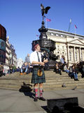 Лондон, Великобритания, 2015-02-23 Шотландский музыкант играя около статуи Anteros на цирке Piccadilly Стоковое Фото