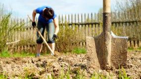 Лопата вставляя в землю при женщина работая на предпосылке Стоковые Изображения RF