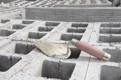 Лопатка на предпосылке серого цвета cinderblock На фоне кирпичной кладки лопатка Стоковое Изображение RF