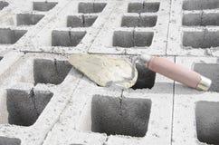 Лопатка на предпосылке серого цвета cinderblock На фоне кирпичной кладки лопатка Стоковые Изображения