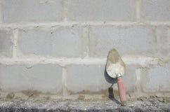 Лопатка на предпосылке серого цвета cinderblock На фоне кирпичной кладки лопатка Стоковые Фотографии RF