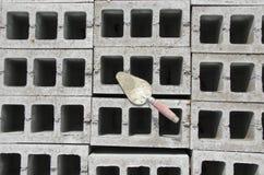 Лопатка на предпосылке серого цвета cinderblock На фоне кирпичной кладки лопатка Стоковая Фотография RF